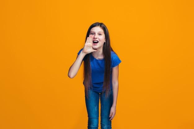 Isolado em amarelo jovem casual adolescente gritando no estúdio