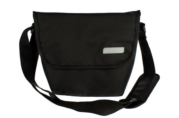 Isolado estúdio tiro de close up de novo pequeno casual moderno moderno na moda tecido preto mensageiro rider homens estilingue bagagem bolsa bolsa com alça e etiqueta cinza vazio na frente do fundo branco.