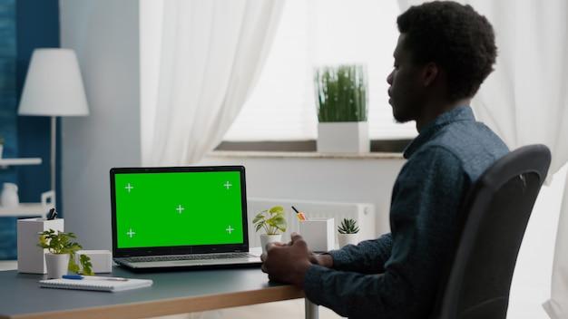 Isolado mock up display no laptop na sala de estar brilhante homem afro-americano trabalhando em casa na g ...