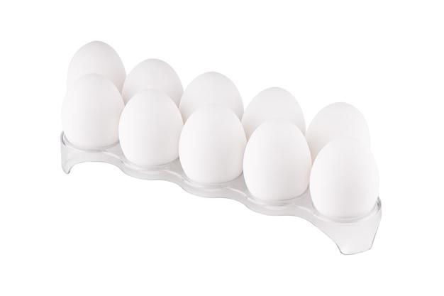 Isolado na pilha branca de ovos de galinha no suporte de plástico.