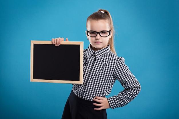 Isolado no azul, atraente caucasiano criança segura grande cartaz vazio