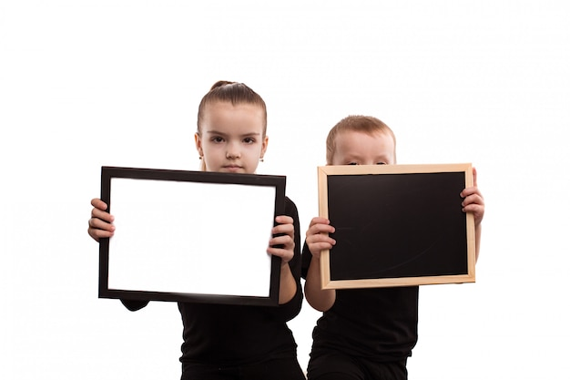 Isolado no fundo branco menino e menina em t-shirts pretas mostram formulários em branco