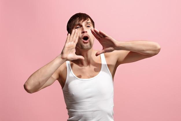 Isolado no jovem casual rosa gritando no estúdio