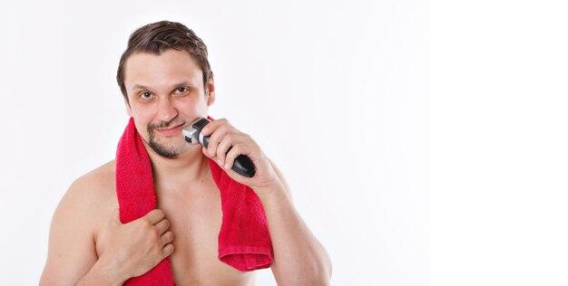 Isolado: um homem raspa a barba por fazer. o cara limpa a barba com um barbeador elétrico. tratamentos matinais no banheiro. toalha vermelha em volta do pescoço. copie o espaço