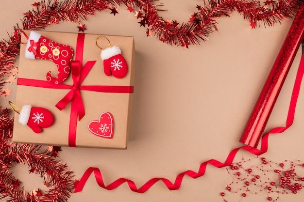 Isolado. um presente embrulhado em papel ofício, com uma fita vermelha na qual repousam meias de doces, luvas e um coração de papel, é cercado por enfeites de natal vermelhos. atmosfera de.