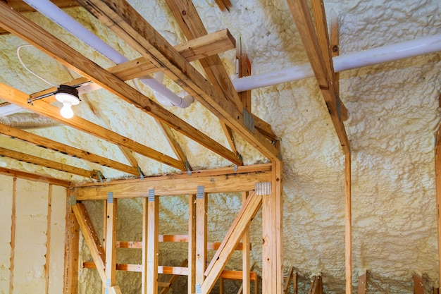 Isolamento de espuma de plástico instalado no teto inclinado da nova casa de madeira.