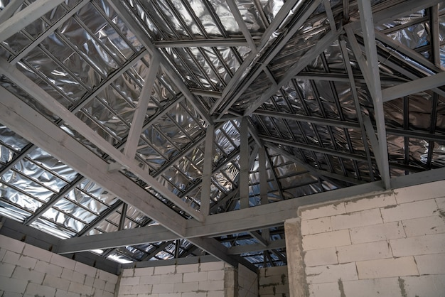 Isolamento de telhado de uma nova casa de telhado de telha com telhado de telha espanhol em construção de casa inacabada, sob a estrutura de telhado