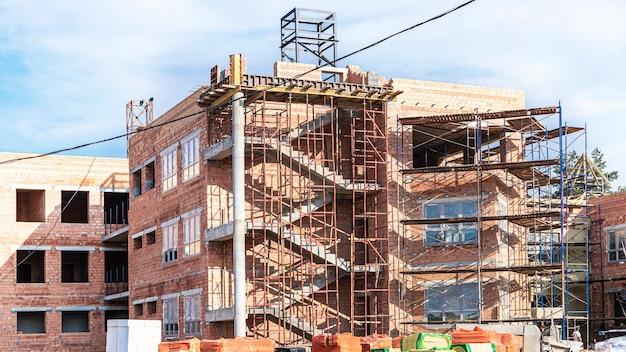 Isolamento térmico de uma casa de tijolos vermelhos com lã mineral. o uso de andaimes na construção de uma casa.