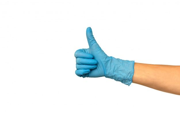 Isole a mão da mulher em uma luva de borracha azul em um fundo branco. gesticule o polegar para cima ou goste. conceito de trabalho bem sucedido de um chef de um cirurgião ou limpeza