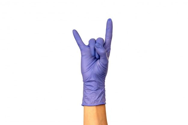 Isole a mão da mulher que mostra dois dedos em uma luva de borracha lilás sobre um fundo branco. gesto que balança ou chifres. o conceito de trabalho bem-sucedido de um chef de cirurgião ou de limpeza