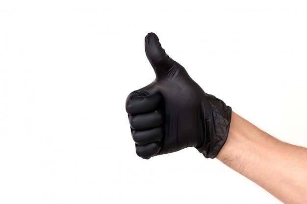 Isole a mão do homem em uma luva de borracha preta sobre um fundo branco. gesticule o polegar para cima ou goste. conceito de trabalho bem sucedido de um chef de um cirurgião ou limpeza