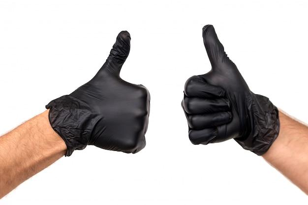Isole a mão dos homens em uma luva de borracha preta em um fundo branco. gesticule o polegar para cima ou goste. conceito de trabalho bem sucedido de um chef de um cirurgião ou limpeza