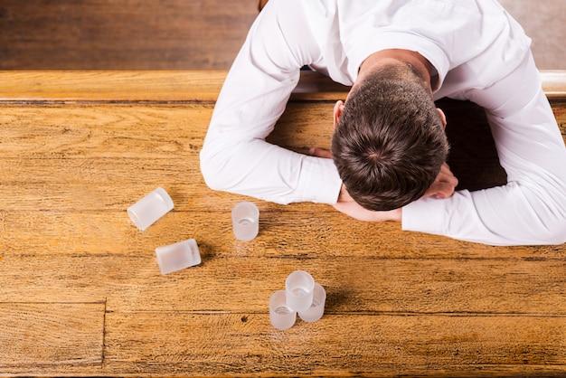 Isso é demais? vista superior de um homem bêbado de camisa branca encostado no balcão do bar enquanto copos vazios em pé perto dele