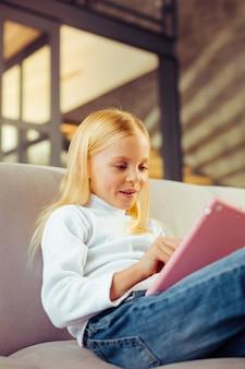 Isso é interessante. menina feliz e positiva mantendo um sorriso no rosto enquanto olha para seu gadget