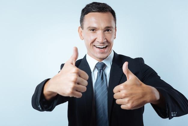 Isso é ótimo. homem alegre, positivo e alegre, sorrindo e mostrando gestos de polegar para cima em pé contra um fundo azul