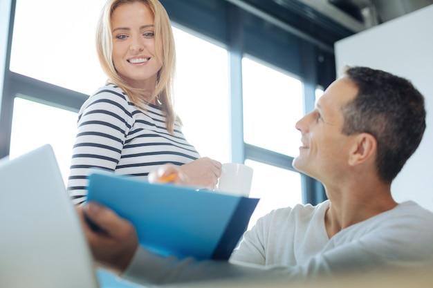 Isso é ótimo. mulher loira positiva e feliz olhando para a pasta azul e aprovando a ideia do colega enquanto trabalhava com ele