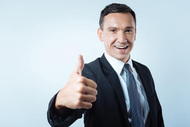 Isso é sucesso. alegre bonita empresária sorrindo e mostrando o polegar para cima enquanto se sente feliz