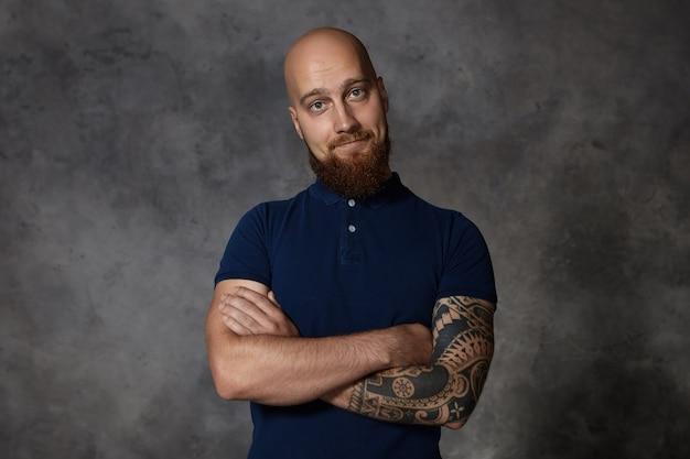 Isso é tão fofo. retrato de um jovem atraente com a barba por fazer, com o corpo musculoso de tatuagem cruzando os braços sobre o peito e sorrindo, sendo tocado por algo ou expressando desconfiança, suspeita e dúvida