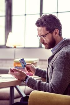 Isso é um sinal. homem sério e pensativo lendo o significado do cartão durante uma sessão de adivinhação