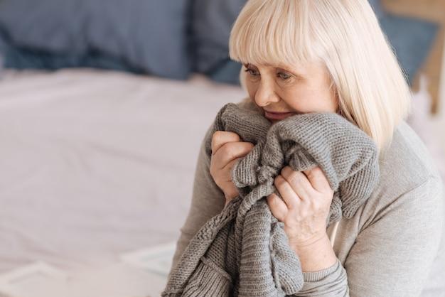 Isso me lembra dele. mulher idosa deprimida e desanimada segurando uma jaqueta de tricô e pronta para explodir em lágrimas enquanto se sente sozinha