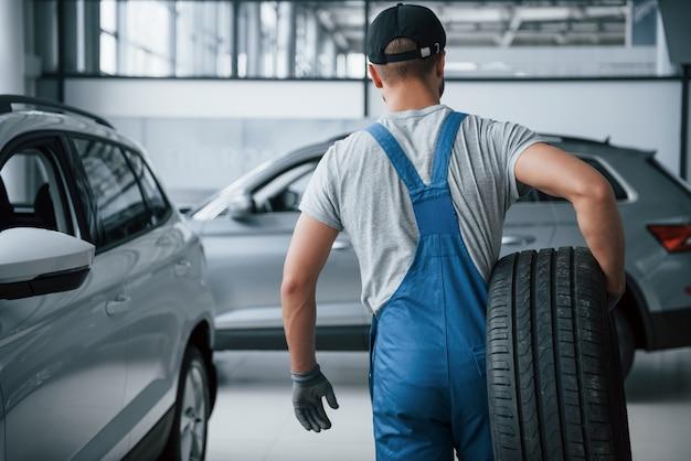 Isso precisa ser removido. mecânico segurando um pneu na oficina. substituição de pneus de inverno e verão