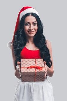 Isto é para você! mulher jovem e atraente com chapéu de papai noel segurando uma caixa de presente e sorrindo em frente ao fundo cinza