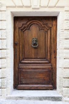 Itália. aldrava antiga na velha porta de madeira.