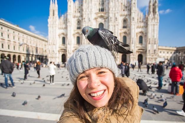 Itália, excursão e conceito de viagens - jovem mulher engraçada tirando selfie com pombos