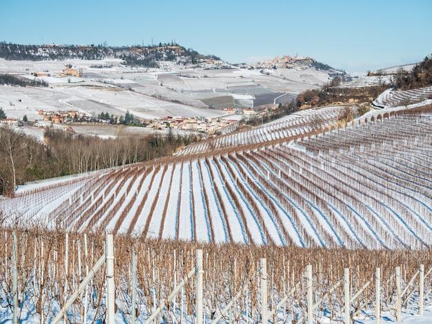 Itália piemonte: fileira de vinícolas, paisagem única no inverno com neve, vila rural no topo da colina