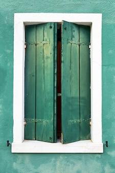 Itália, veneza, ilha de burano. paredes coloridas tradicionais e janelas das casas antigas. copie o espaço