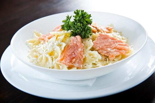 Italiano salmão frito e penne rigate com molho de macarrão cremoso de espinafre alfredo