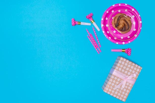 Itens de aniversário rosa sobre fundo azul, com espaço de cópia