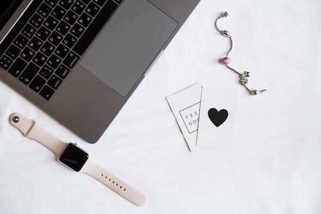 Itens de área de trabalho: laptop, relógio inteligente, acessórios de mulher, vista superior