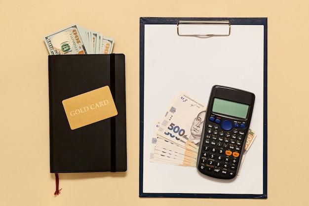 Itens de conceito de negócio no diário de mesa, dólares, cartão ouro, calculadora, sobre um fundo bege. bitcoins são uma moeda digital, o mercado global de comércio e troca de dinheiro.