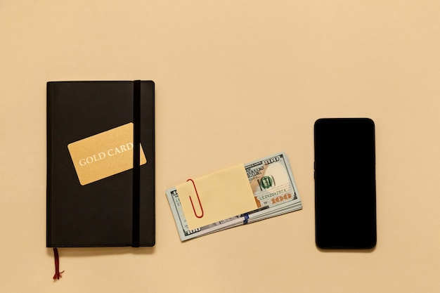 Itens de conceito de negócio no diário de mesa, dólares, cartão ouro, telefone, sobre um fundo bege. bitcoins são uma moeda digital, o mercado global de comércio e troca de dinheiro.