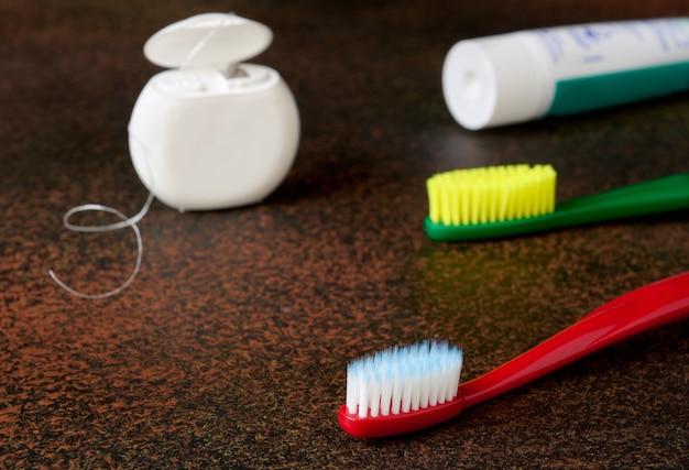 Itens de higiene bucal com fundo escuro close-up, escovas de dente, fio dental
