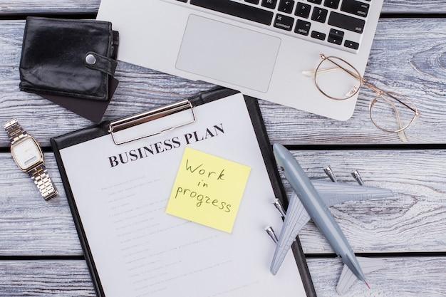 Itens de negócios e nota de trabalho em andamento. clipbpard plano leigo com plano de negócios com carteira e laptop em madeira branca.