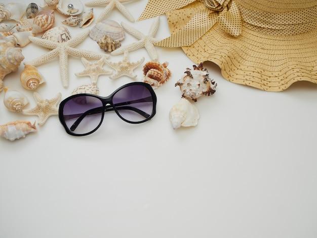 Itens de vestido de praia verão - conchas, estrela do mar, óculos escuros, chapéus de palha em um fundo branco