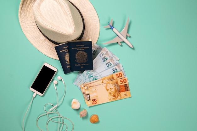 Itens para as férias de verão: telefone, passaporte, dinheiro e avião. fundo azul, vista superior