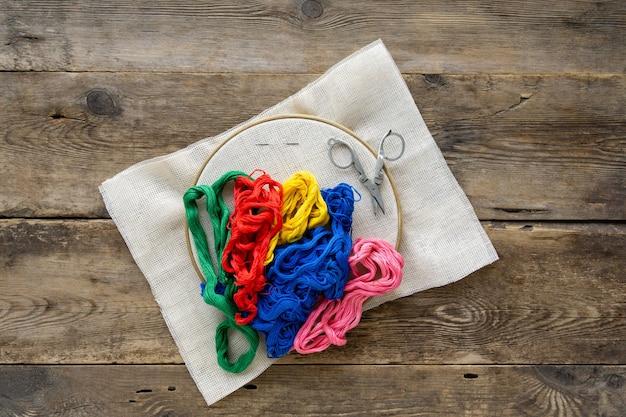 Itens para bordados. aro, fios de fio dental coloridos e tela em madeira velha.