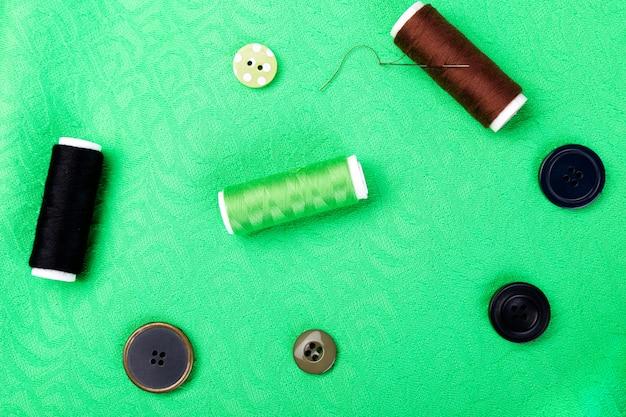 Itens para costura de roupas. botões de costura, carretéis de linha e tecido. vista do topo.