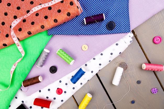 Itens para costurar roupas. botões de costura, carretéis de linha e pano. vista do topo.