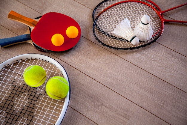 Itens para fitness, raquetes e acessórios para badminton, tênis de mesa e tênis em um fundo de madeira