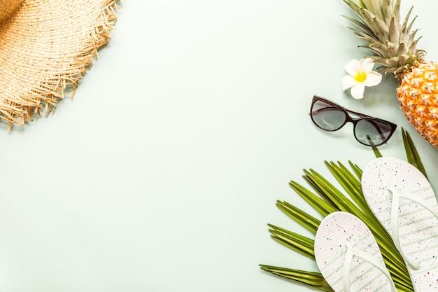 Itens planos de viagem: abacaxi fresco, chapéu de palha grande, óculos de sol, plumeria de flores tropicais e folha de palmeira.