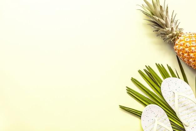 Itens planos de viagem: abacaxi fresco, sapatos de praia e folha de palmeira.