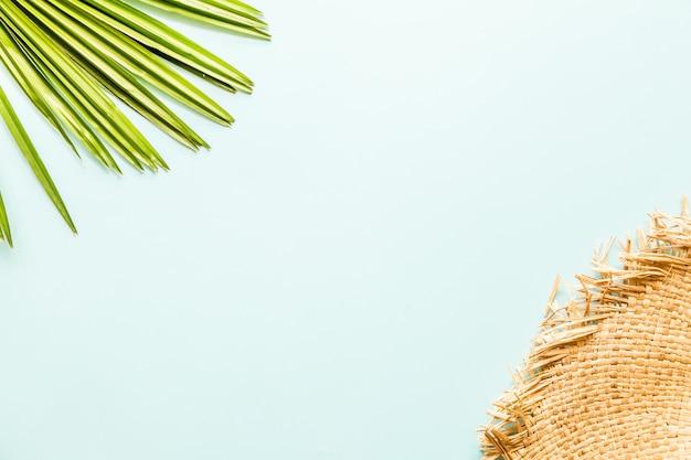 Itens planos de viagem: grande chapéu de palha e folha de palmeira.