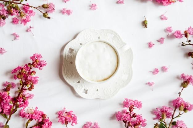 Itens planos leigos: caneca de café e flores cor de rosa na mesa branca