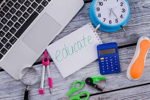 Itens planos para estudar e educar. pc laptop com tesoura de calculadora e grampeador na mesa de madeira branca.