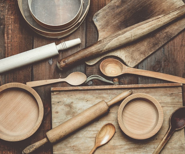 Itens vintage de cozinha de madeira: peneira, rolo, colheres vazias e pratos redondos na mesa de madeira marrom, vista de cima