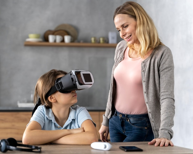 Ittle girl com fone de ouvido de realidade virtual com a mãe ao lado